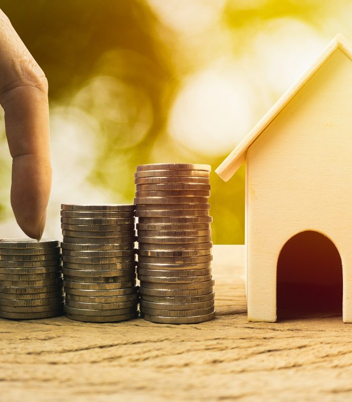 Real estate investment, home loan, savings to buy home concepts. House wooden model , Fingers climb on coins. depicts a funding or growing money for real estate investment.