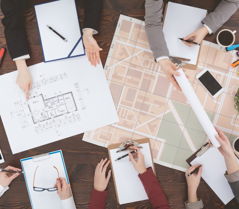 Workers of real estate agency analyzing architecture project, top view